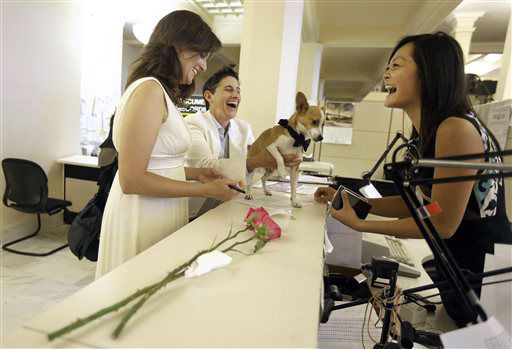 Assessor-Recorder Carmen Chu, right, laughs as Jen, left, and Frances Rainin&#39;s dog Punum climbs on the counter as they fill out paper work for their marriage certificate after they were married at City Hall in San Francisco, Friday, June 28, 2013. A three-judge panel of the 9th U.S. Circuit Court of Appeals issued a brief order Friday afternoon dissolving, &#34;effective immediately,&#34; a stay it imposed on gay marriages while the lawsuit challenging the ban advanced through the courts.  <span class=meta>(AP Photo&#47; Jeff Chiu)</span>
