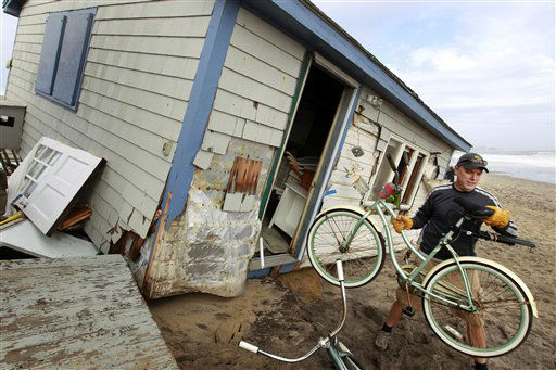 Pete Duhamel, of South Kingstown, R.I. removes a bicycle from a cottage while helping a friend salvage belongings from the structure destroyed by Superstorm Sandy, on Roy Carpenter&#39;s Beach, in the village of Matunuck, in South Kingstown, Tuesday, Oct. 30, 2012. Sandy, the storm that made landfall Monday, caused multiple fatalities, halted mass transit and cut power to more than 6 million homes and businesses.   <span class=meta>(AP Photo&#47; Steven Senne)</span>