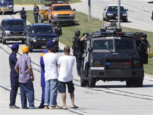 People watch police personnel outside the Sikh Temple in Oak Creek, Wis., where a shooting took place Sunday, Aug 5, 2012.   <span class=meta>(AP Photo&#47; JEFFREY PHELPS)</span>