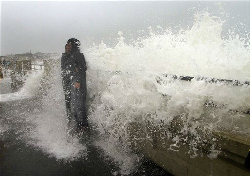 "<div class=""meta ""><span class=""caption-text "">A couple posing for a picture get hit by a wave in Hampton, N.H., from the effects of Hurricane Sandy Monday, Oct. 29, 2012. The hurricane continued on its path Monday, as the storm forced the shutdown of mass transit, schools and financial markets, sending coastal residents fleeing, and threatening a dangerous mix of high winds and soaking rain.  (AP Photo/ Jim Cole)</span></div>"