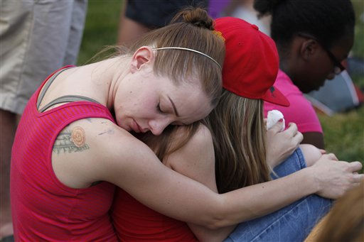Jacqueline Bailey, left, holds onto her sister Kaylan Bailey, both from Aurora, Sunday, July 22, 2012, in Aurora, Colo., during a prayer vigil for the victims of Friday&#39;s mass shooting at a movie theater. Twelve people were killed and dozens were injured in a shooting attack Friday at the packed theater during a showing of the Batman movie, &#34;The Dark Knight Rises.&#34; Police have identified the suspected shooter as James Holmes, 24. &#40;AP Photo&#47;Alex Brandon&#41; <span class=meta>(AP Photo&#47; Alex Brandon)</span>