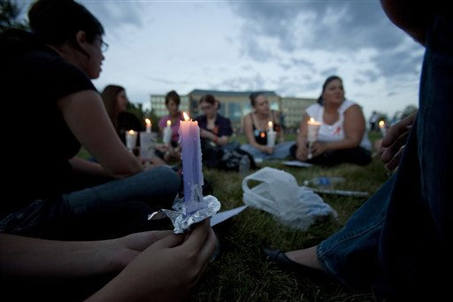 "<div class=""meta ""><span class=""caption-text "">A group of friends with various connections to the deceased and wounded gather at a prayer vigil  outside the Aurora Municipal Center in Aurora, Colo., Sunday July 22, 2012.   The vigil was held to remember the dead and injured in the  shooting rampage Friday at movie theater in in Aurora. (AP Photo/Barry Gutierrez) (AP Photo/ Barry Gutierrez)</span></div>"
