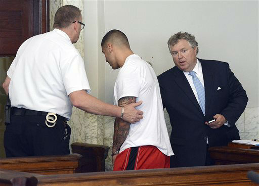 Former New England Patriots tight end Aaron Hernandez, center, is led away, as his attorney Michael Fee speaks to him, right, after arraignment in Attleboro District Court Wednesday, June 26, in Attleboro, Mass. Hernandez was charged with murdering Odin Lloyd, a 27-year-old semi-pro football player for the Boston Bandits, whose body was found June 17 in an industrial park in North Attleborough, Mass.     <span class=meta>(AP Photo&#47; Mike George)</span>