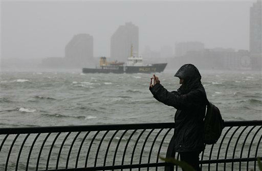 A woman uses her mobile phone to photograph New York Harbor at Battery Park, at the southern tip of Manhattan, Monday, Oct. 29, 2012. Defiant New Yorkers jogged, pushed strollers and took snapshots of churning New York Harbor on Monday, trying to salvage normal routines in a city with no trains, schools and an approaching mammoth storm.  <span class=meta>(AP Photo&#47; Richard Drew)</span>