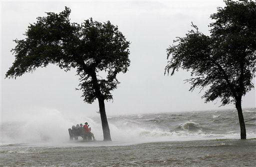 People sit on a bench along the seawall in the storm surge from Isaac, on Lakeshore Drive along Lake Pontchartrain, as the storm approaches landfall, in New Orleans, Tuesday, Aug. 28, 2012.   <span class=meta>(AP Photo&#47; Gerald Herbert)</span>