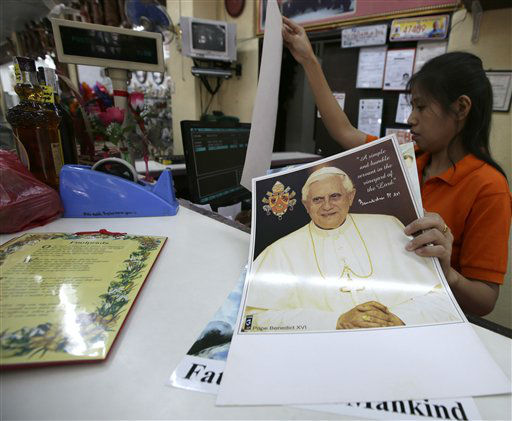 A Filipino salesclerk checks the price of posters, including that of Pope Benedict XVI, at a religious store in Manila, Philippines Thursday Feb. 28, 2013. Pope Benedict XVI formally resigns Thursday, the first pope to abdicate the papacy in 600 years. <span class=meta>(AP photo)</span>
