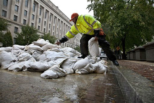 As rain from Hurricane Sandy arrives in Washington, Rick Campbell of Upper Marlboro, Md., reaches for sandbags to shore up vulnerable spots at The Pavilion at the Old Post Office, Monday, Oct. 29, 2012. The Justice Department is seen in the background. &#40;AP Photo&#47;J. Scott Applewhite&#41; <span class=meta>(AP Photo&#47; J. Scott Applewhite)</span>