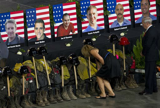 "<div class=""meta ""><span class=""caption-text "">Photos of some of the 19 fallen firefighters line the front of the stage before a memorial service at Tim's Toyota Center in Prescott Valley, Ariz. on Tuesday, July 9, 2013.   Prescott's Granite Mountain Hotshots were overrun by smoke and fire while battling a blaze on a ridge in Yarnell, about 80 miles northwest of Phoenix on June 30, 2013.     (AP Photo/ MICHAEL CHOW)</span></div>"