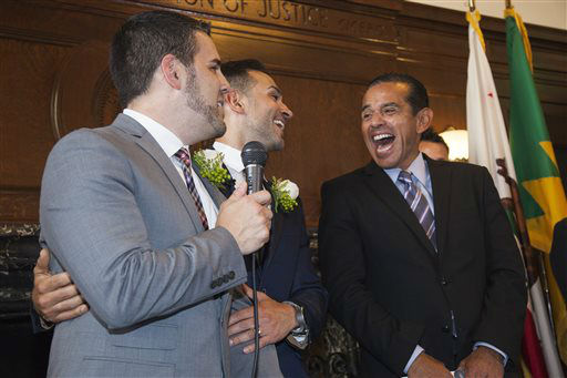 CORRECTS BYLINE TO RICHARD VOGEL - Jeff Zarrillo, left, and Paul Katami laugh with Los Angeles Mayor Antonio Villaraigosa, right, after they were married by the mayor Friday June 28, 2013 at City Hall in Los Angeles. A three-judge panel of the 9th U.S. Circuit Court of Appeals issued a brief order Friday afternoon dissolving, &#34;effective immediately,&#34; a stay it imposed on gay marriages while the lawsuit challenging the ban advanced through the court.   <span class=meta>(AP Photo&#47; Richard Vogel)</span>