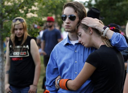 CORRECTS SPELLING TO FRANKLIN - Kenton Copple, left, from Arvada, comforts Emma Franklin, from Denver, Sunday, July 22, 2012, in Aurora, Colo., during a prayer vigil for the victims of Friday&#39;s mass shooting at a movie theater. Twelve people were killed and dozens were injured in a shooting attack Friday at the packed theater during a showing of the Batman movie, &#34;The Dark Knight Rises.&#34; Police have identified the suspected shooter as James Holmes, 24. &#40;AP Photo&#47;Alex Brandon&#41; <span class=meta>(AP Photo&#47; Alex Brandon)</span>