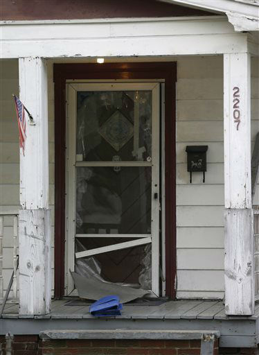 The front door of a house where three women escaped is shown Tuesday, May 7, 2013, in Cleveland. Amanda Berry, Gina DeJesus and Michelle Knight, who went missing separately about a decade ago, were found in the home just south of downtown Cleveland Monday, May 6, and likely had been tied up during years of captivity, said police, who arrested three brothers.  <span class=meta>(AP Photo&#47; Tony Dejak)</span>