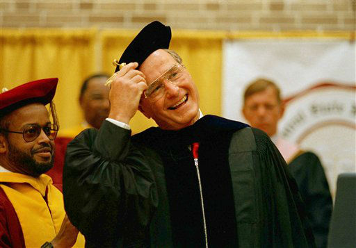 "<div class=""meta ""><span class=""caption-text "">U.S. Vice President George Bush adjusts his cap after receiving an honorary Doctor of Law degree along with the graduating class at Central State University in Wilberforce, Ohio, June 12, 1988. (AP Photo/ David Kohl)</span></div>"