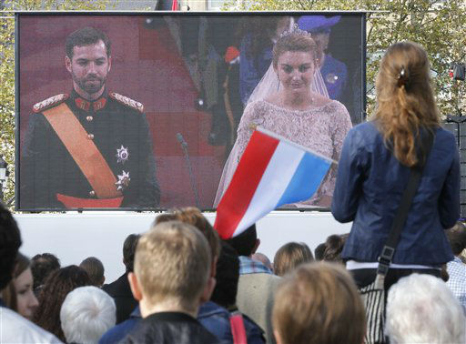 "<div class=""meta ""><span class=""caption-text "">A girl waves a Luxembourg flag is she watches the royal wedding in the cathedral on a video screen on a square in Luxembourg, Saturday, Oct. 20, 2012. Heir to the throne Prince Guillaume celebrates his religious wedding with Belgium's Countess Stephanie de Lannoy.(AP Photo/Michael Probst) (AP Photo/ Michael Probst)</span></div>"