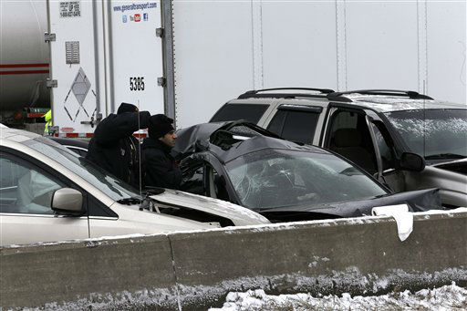 Authorities search a section of multi-vehicle accident on Interstate 75 is shown in Detroit, Thursday, Jan. 31, 2013. Snow squalls and slippery roads led to a series of accidents that left at least three people dead and 20 injured on a mile-long stretch of southbound I-75. More than two dozen vehicles, including tractor-trailers, were involved in the pileups.   <span class=meta>(AP Photo&#47; Paul Sancya)</span>