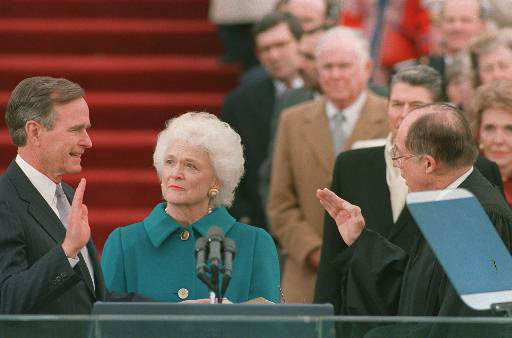 President George Bush raises his right hand as he is sworn into office as the 41st president of the United States by Chief Justice William Rehnquist outside the west front of the Capitol on Jan. 20, 1989.  First lady Barbara Bush holds the bible for her husband.  Former President Reagan is in the background.  &#40;AP Photo&#47;Bob Daugherty&#41; <span class=meta>(AP Photo&#47; BOB DAUGHERTY)</span>