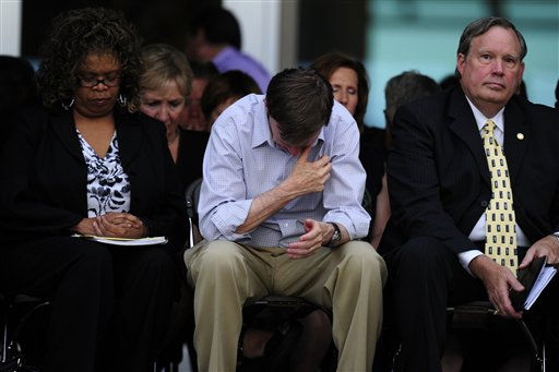 Gov. John Hickenlooper, center, bows his head Sunday, July 22, 2012, in Aurora, Colo., at a prayer vigil for the victims of Friday&#39;s mass shooting at a movie theater. 12 people were killed and 58 were injured in a shooting during an early Friday premiere of ?The Dark Knight Rises.&#34; &#40;AP Photo&#47;The Denver Post, AAron Ontiveroz, Pool&#41; <span class=meta>(AP Photo&#47; AAron Ontiveroz)</span>