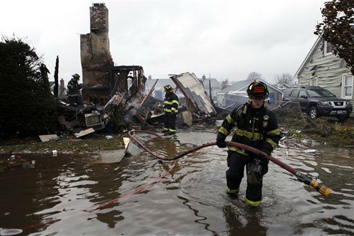 Firefighters work at the scene of a house fire in the aftermath of superstorm Sandy, Tuesday, Oct. 30, 2012, in Lindenhurst, N.Y. According to firefighters at the scene, four homes were destroyed by fire overnight in Lindenhurst, and six in Massapequa. &#40;AP Photo&#47;Jason DeCrow&#41; <span class=meta>(AP Photo&#47; Jason DeCrow)</span>