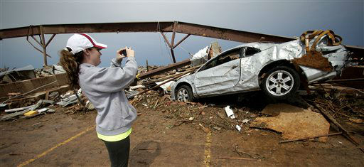 Heather Walker takes a photo of her tornado-ravaged car outside the day care where she works Tuesday, May 21, 2013, in Moore, Okla. A huge tornado roared through the Oklahoma City suburb Monday, flattening entire neighborhoods and destroying an elementary school with a direct blow as children and teachers huddled against winds. Seven adults and thirteen children rode survived the tornado by huddling in the daycare&#39;s bathroom.   <span class=meta>(AP Photo&#47; Charlie Riedel)</span>