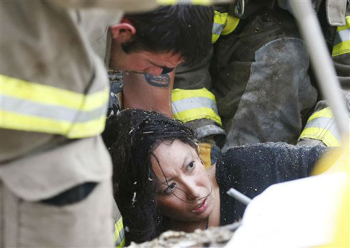 A woman is pulled out from under tornado debris at the Plaza Towers School in Moore, Okla., Monday, May 20, 2013. A tornado as much as a mile &#40;1.6 kilometers&#41; wide with winds up to 200 mph &#40;320 kph&#41; roared through the Oklahoma City suburbs Monday, flattening entire neighborhoods, setting buildings on fire and landing a direct blow on an elementary school.&#40;AP Photo Sue Ogrocki&#41; <span class=meta>(AP Photo&#47; Sue Ogrocki)</span>