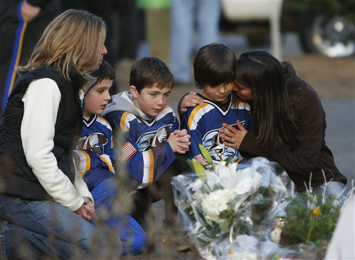 From left, Jean Bradley, Steven Turchetta, 9, Jean's son Matthew Bradley, 9, Ashton Baltes, 10, and his mother Elonda Baltes pay their respects at a memorial for shooting victims near Sandy Hook Elementary School, Saturday, Dec. 15, 2012 in Newtown, Conn. A gunman walked into Sandy Hook Elementary School in Newtown Friday and opened fire, killing 26 people, including 20 children. The three friends play on the same hockey team, and wanted to visit the memorial Saturday after having played a hockey game nearby. (AP Photo/Jason DeCrow)