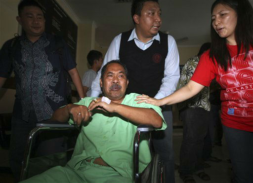A passenger injured in a plane crash in a wheelchair is carried for medical treatment at a hospital in Jimbarn, Bali, Indonesia, Saturday, April 13, 2013. A Lion Air plane carrying more than 100 passengers and crew overshot a runway on the Indonesian resort island of Bali on Saturday and crashed into the sea, injuring nearly two dozen people, officials said.   <span class=meta>(AP Photo&#47; Firdia Lisnawati)</span>