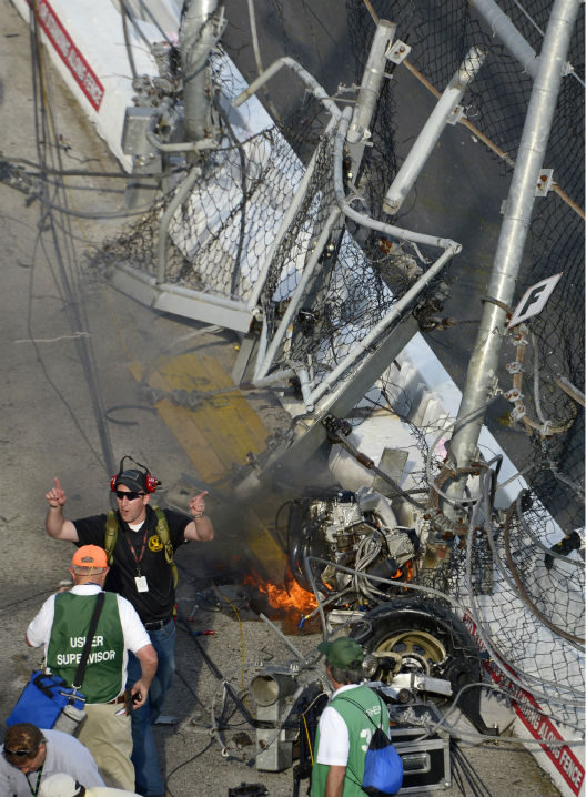 An emergency official ushers fans away from driver Kyle Larson&#39;s engine as it burns behind the wall and safety fence that he hit along the front grandstands on the final lap of the NASCAR Nationwide Series auto race at Daytona International Speedway in Daytona Beach, Fla., Saturday, Feb. 23, 2013. &#40;AP Photo&#47;Phelan M. Ebenhack&#41; <span class=meta>(AP Photo&#47; Phelan M. Ebenhack)</span>