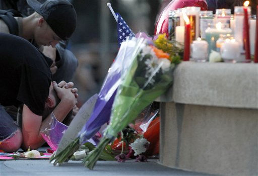 A man holds his head in front of a memorial after a pray vigil Sunday, July 22, 2012 in Aurora, Colo. Twelve people were killed and dozens were injured in a shooting attack early Friday at the packed theater during a showing of the Batman movie, &#34;The Dark Knight Rises.&#34; Police have identified the suspected shooter as James Holmes, 24. &#40;AP Photo&#47;Alex Brandon&#41; <span class=meta>(AP Photo&#47; Alex Brandon)</span>