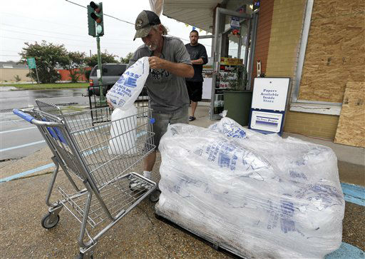 John Taylor loads a cart with ice for a customer Tuesday, Aug. 28, 2012, in Chalmette, La. The U.S. National Hurricane Center in Miami said Isaac became a Category 1 hurricane Tuesday with winds of 75 mph. It could get stronger by the time it&#39;s expected to reach the swampy coast of southeast Louisiana.   <span class=meta>(AP Photo&#47; David J. Phillip)</span>