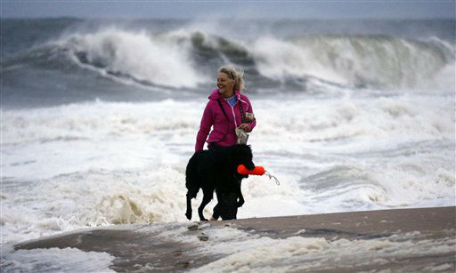 Annemarie Jarman, and her dog &#34;Bruges,&#34; walk along the edge of the beach that is mostly empty as Hurricane Sandy bears down on the east coast, Saturday, Oct. 27, 2012, in Ocean City, Md. Hurricane Sandy, upgraded again Saturday just hours after forecasters said it had weakened to a tropical storm, was barreling north from the Caribbean and was expected to make landfall early Tuesday near the Delaware coast, then hit two winter weather systems as it moves inland, creating a hybrid monster storm. &#40;AP Photo&#47;Alex Brandon&#41; <span class=meta>(AP Photo&#47; Alex Brandon)</span>