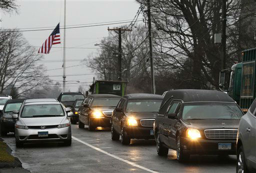 A hearse and family limousines for six-year-old shooting victim Jack Pinto rolls past a flag at half staff as the funeral procession heads through the historic district in Newtown, Conn., Monday, Dec. 17, 2012. A gunman opened fire on Friday at Sandy Hook Elementary School in the town, killing 26 people, including 20 children before killing himself. &#40;AP Photo&#47;Charles Krupa&#41; <span class=meta>(AP Photo&#47; Charles Krupa)</span>