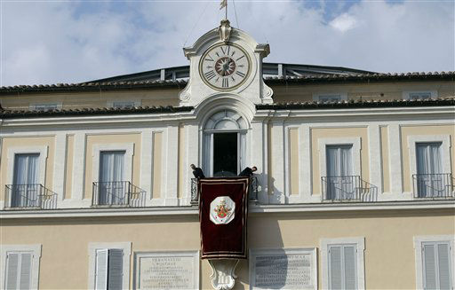 Vatican workers hang the tapestry from the window of the pope&#39;s summer residence in Castel Gandolfo, the scenic town where Pope Benedict XVI will spend his first post-Vatican days and make his last public blessing as pope,Thursday, Feb. 28, 2013. <span class=meta>(AP photo)</span>