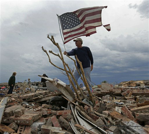 "<div class=""meta ""><span class=""caption-text "">Jim Stubblefield, of Norman, Okla., raises a tattered flag he found while helping his sister salvage items from her tornado-ravaged home Tuesday, May 21, 2013, in Moore, Okla. A huge tornado roared through the Oklahoma City suburb Monday, flattening entire neighborhoods and destroying an elementary school with a direct blow as children and teachers huddled against winds.  (AP Photo/ Charlie Riedel)</span></div>"