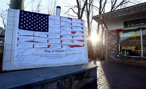 Light peeks through as the sun rises next to a U.S. flag covered with numbers representing the people that died when a gunman opened fired at Sandy Hook Elementary School during a shooting rampage a day earlier, Saturday, Dec. 15, 2012, in Sandy Hook village of Newtown, Conn. The massacre of 26 children and adults at Sandy Hook Elementary school elicited horror and soul-searching around the world even as it raised more basic questions about why the gunman, 20-year-old Adam Lanza, would have been driven to such a crime and how he chose his victims.    <span class=meta>(AP Photo&#47; Julio Cortez)</span>