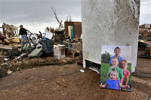 "<div class=""meta ""><span class=""caption-text "">Rodney Heltcel, left, salvages the wreckage of his home for photos and irreplaceable items, such as the print of his grandchildren he placed at right, a day after a tornado moved through Moore, Okla., Tuesday, May 21, 2013. The huge tornado roared through the Oklahoma City suburb, flattening entire neighborhoods and destroying an elementary school with a direct blow as children and teachers huddled against winds.  (AP Photo/ Brennan Linsley)</span></div>"