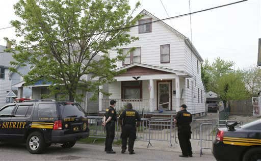 "<div class=""meta image-caption""><div class=""origin-logo origin-image ""><span></span></div><span class=""caption-text"">Sheriff deputies stand outside a house in Cleveland Tuesday, May 7, 2013, the day after three women who vanished a decade ago were found there. Amanda Berry, Gina DeJesus and Michelle Knight, who went missing separately about a decade ago, were found in the home just south of downtown Cleveland and likely had been tied up during years of captivity, said police, who arrested three brothers.  (AP Photo/ Tony Dejak)</span></div>"
