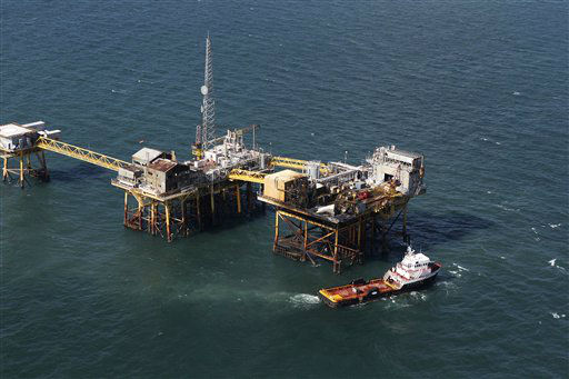 In this aerial photograph, a supply vessel moves near an oil rig damaged by an explosion and fire, Friday, Nov. 16, 2012, in the Gulf of Mexico about 25 miles southeast of Grand Isle, La. Four people were transported to a hospital with critical burns and two were missing. &#40;AP Photo&#47;Gerald Herbert&#41; <span class=meta>(AP Photo&#47; Gerald Herbert)</span>