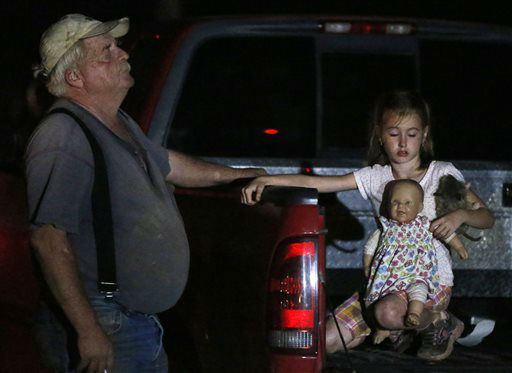 Seven-year-old Katrina Ash, right, holds a doll as she waits in the back of a truck with her grandfather, Michael Bowen, left, after a tornado ripped through their neighborhood near Dale, Okla., Sunday, May 19, 2013. Residents are not being allowed back into the neighborhood as search and rescue efforts take place. &#40;AP Photo Sue Ogrocki&#41; <span class=meta>(AP Photo&#47; Sue Ogrocki)</span>