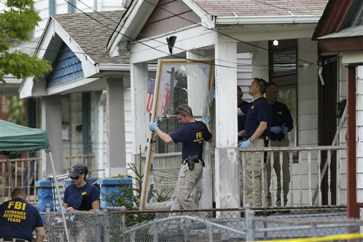 Members of the FBI evidence response team carry out the front screen door from a house Tuesday, May 7, 2013, where three women were held, in Cleveland. Three women who disappeared a decade ago were found safe Monday, and police arrested three brothers accused of holding the victims against their will.   <span class=meta>(AP Photo&#47; Tony Dejak)</span>