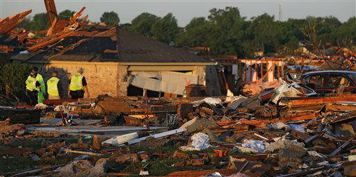 At sunrise, police patrol a partially-destroyed row of houses adjacent to a group of homes completely leveled on Monday when a tornado moved through Moore, Okla., Wednesday, May 22, 2013. The huge tornado roared through the Oklahoma City suburb, flattening a wide swath of homes and businesses.  <span class=meta>(AP Photo&#47; Brennan Linsley)</span>
