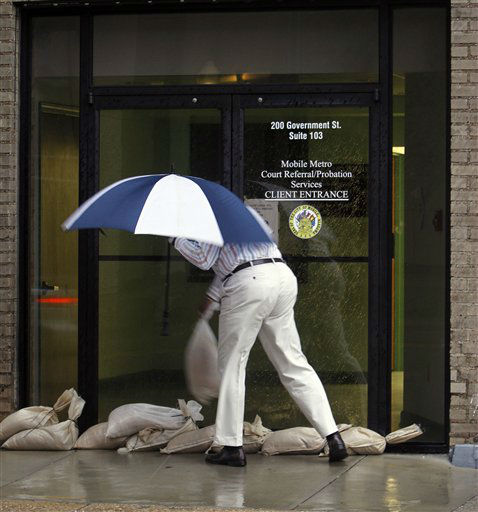 A man removes sand bags from the entrance to an office as he arrived to work in Mobile, Ala. on Wednesday, Aug. 29, 2012.  Hurricane Isaac has dumped more than five inches of rain on the Alabama coast and knocked out power to some residents, but it hasn&#39;t interrupted the everyday life of others.  Residents of Dauphin Island lost power, but they also escaped the worst of Isaac. The weather service reports wind gusts of 47 mph. <span class=meta>(AP Photo&#47; Butch Dill)</span>