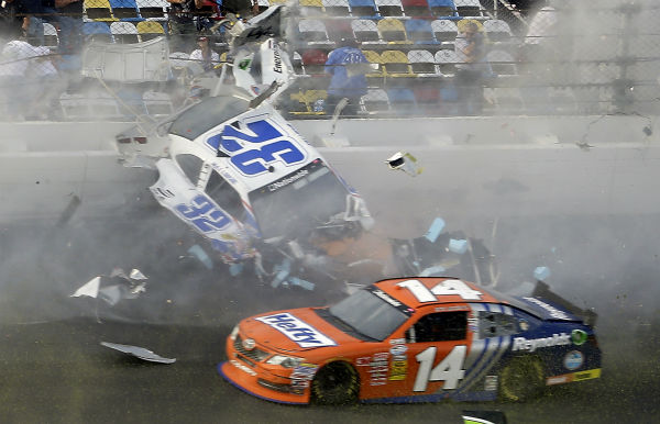Kyle Larson &#40;32&#41; slides along the wall after hitting the catch fence as Eric McClure &#40;14&#41; goes low after the cars were involved in a multi-car crash on the final lap of the NASCAR Nationwide Series auto race at Daytona International Speedway, Saturday, Feb. 23, 2013, in Daytona Beach, Fla. &#40;AP Photo&#47;John Raoux&#41; <span class=meta>(AP Photo&#47; John Raoux)</span>