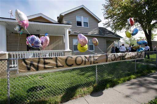 A &#34;Welcome Home Gina &#34; sign hangs on a fence outside the home of Gina DeJesus Tuesday, May 7, 2013, in Cleveland. DeJesus, Amanda Berry and Michelle Knight, who went missing separately about a decade ago, were found in a home just south of downtown Cleveland and likely had been tied up during years of captivity, said police, who arrested three brothers.  <span class=meta>(AP Photo&#47;Tony Dejak)</span>
