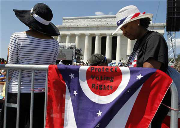"<div class=""meta ""><span class=""caption-text "">Sarah Lee of Columbus, Ohio, right, stands next to a Ohio state flag she brought to the rally to commemorate the 50th anniversary of the 1963 March on Washington on the steps of the Lincoln Memorial on Saturday, Aug. 24, 2013, in Washington. (AP Photo/Jon Elswick) (Photo/Jon Elswick)</span></div>"
