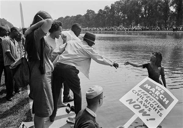 Kathleen Johnson of Newark, N.J. gets help from unidentified members of the crowd assembled near the Lincoln Memorial as part of the March On Washington, Aug. 28, 1963. Mrs. Johnson fell into the reflecting pool near the memorial while trying to take a photograph of the area.  (AP Photo)