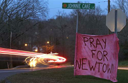 Tail lights streak past a sign asking for prayer on Main Street heading into the village of Newtown, Conn., at dusk Saturday, Dec. 15, 2012. A gunman opened fire at Sandy Hook Elementary School in the town, killing 26 people, including 20 children before killing himself on Friday. &#40;AP Photo&#47;Charles Krupa&#41; <span class=meta>(Photo&#47;Charles Krupa)</span>