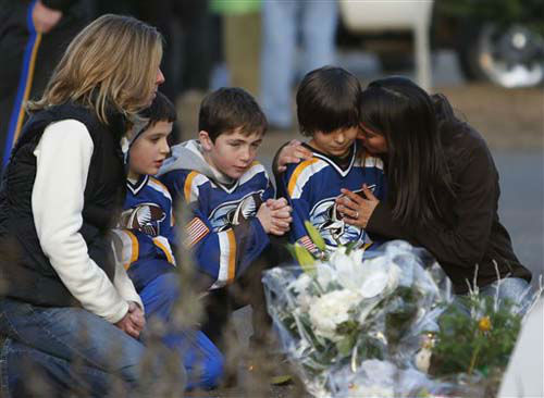From left, Jean Bradley, Steven Turchetta, 9, Jean&#39;s son Matthew Bradley, 9, Ashton Baltes, 10, and his mother Elonda Baltes pay their respects at a memorial for shooting victims near Sandy Hook Elementary School, Saturday, Dec. 15, 2012 in Newtown, Conn.  A gunman walked into Sandy Hook Elementary School in Newtown Friday and opened fire, killing 26 people, including 20 children.  The three friends play on the same hockey team, and wanted to visit the memorial Saturday after having played a hockey game nearby. &#40;AP Photo&#47;Jason DeCrow&#41; <span class=meta>(Photo&#47;Jason DeCrow)</span>