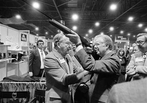 Former President Jimmy Carter sights down the barrel of a shotgun as Reinhart Fajen, a gunstock manufacturer checks the fit, Thursday, Nov. 14, 1984 in Atlanta as Carter stopped during a visit to the national shooting sports foundation shot show at the World Congress center. (AP Photo/Ric Feld)