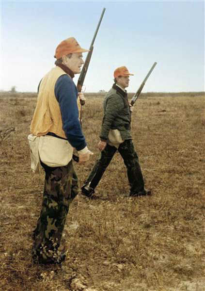 President George H.W. Bush, left, and Will Farish hunt quail December 28, 1989 on the Lazy F Ranch near Beeville, Texas. Bush is spending the New Year holiday in Texas before returning to Washington. (AP Photo/ White House Photo by David Valdez)