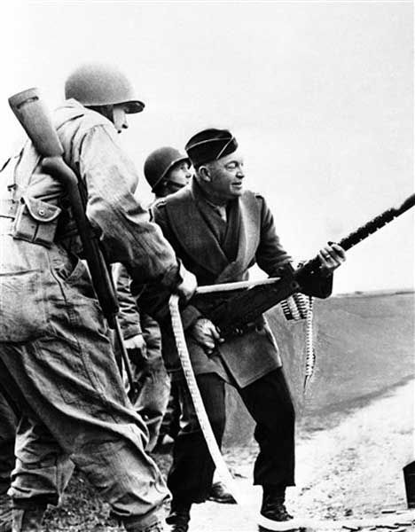 Gen. Dwight D. Eisenhower, Allied invasion chief, fires a Browning light machine gun using his hip as a mount, during an inspection of an infantry unit in England on Feb. 28, 1944. (AP Photo)