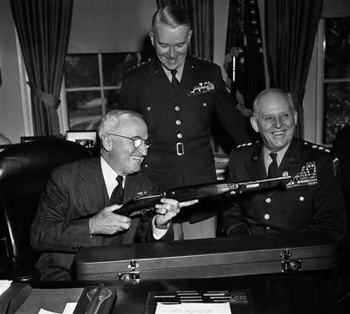 President Harry Truman shoulders an army carbine rifle given to him in his office in Washington on Nov. 28, 1950 by Gen. Clarence R. Huebner (right), retiring commander of U.S. forces in Europe. Gen. J. Lawton Collins, army chief of staff, is at center. (AP Photo/Byron Rollins)